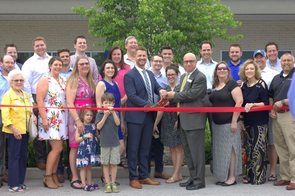 Group of men and women at a ribbon cutting
