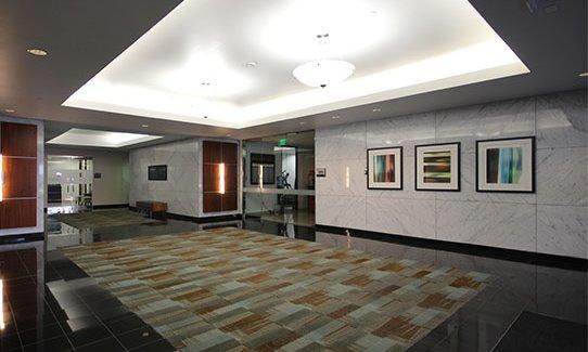 office lobby with ceramic walls and 3 large paintings, large earth tone rug atop marble floor.
