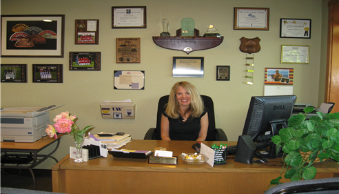 Isabelle sits at her desk in the office smiling at the camera with a wall of awards behind her