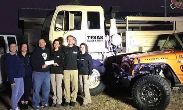 Six adults posing with a check for a charity in front of large trucks.