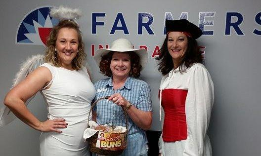 Three people in costume posing in front of Farmers logo