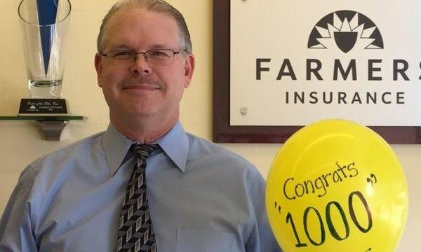 "Agent standing with a yellow balloon with ""Congrats 1000"" written on it"