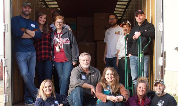 Agent standing in the back of a moving truck with a large group