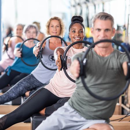 A line of Club Pilates members doing stretches with a Pilates Circle