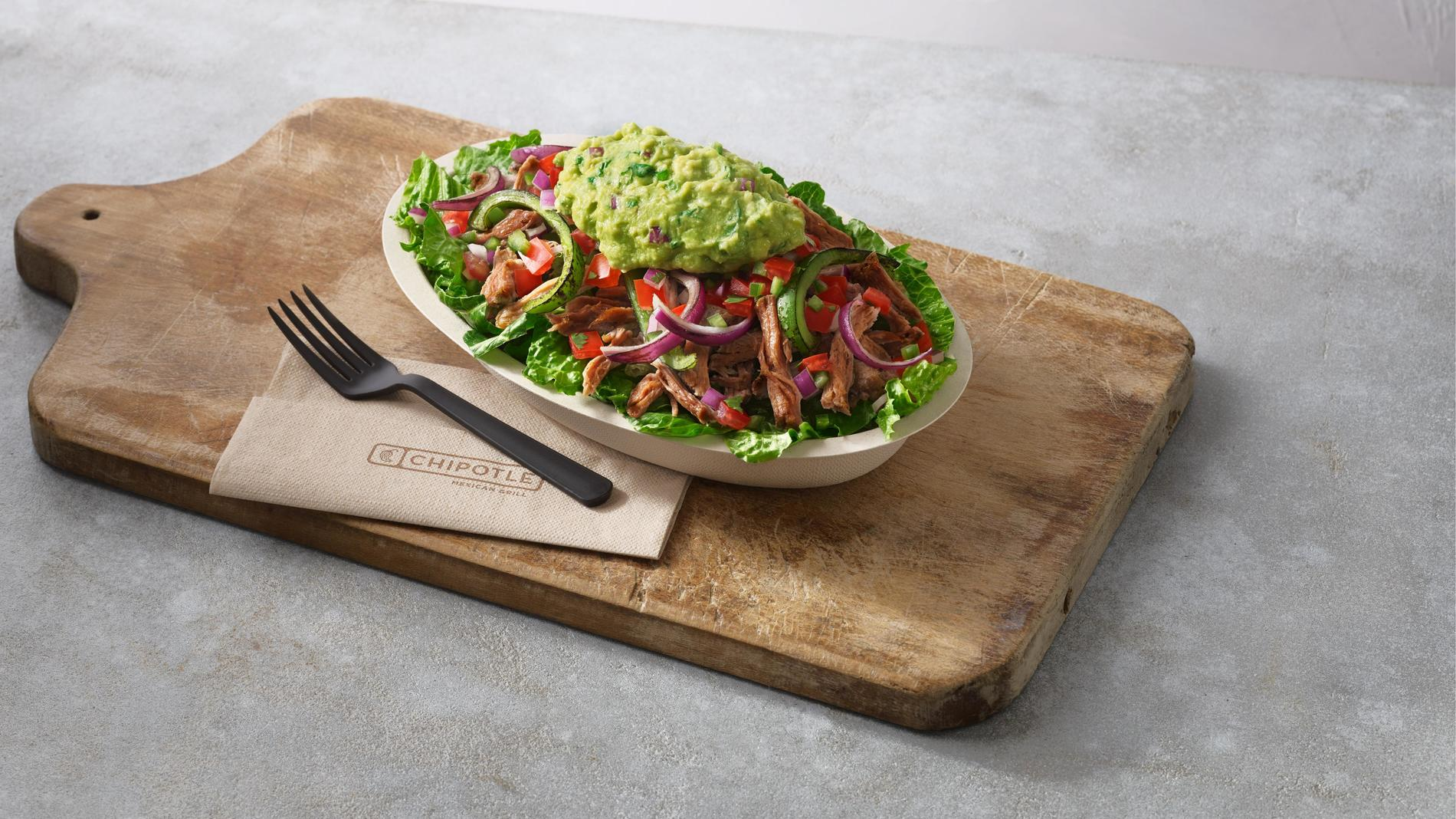 Whole30 salad bowl on a wooden cutting board with a fork and napkin