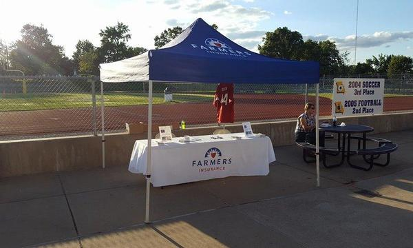 A Farmers Insurance tent in front of a track and field.