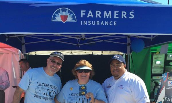 Agent standing with a man and a woman under a Farmers® tent