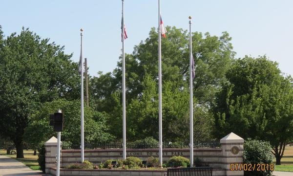 A photo of four flag poles in a park.