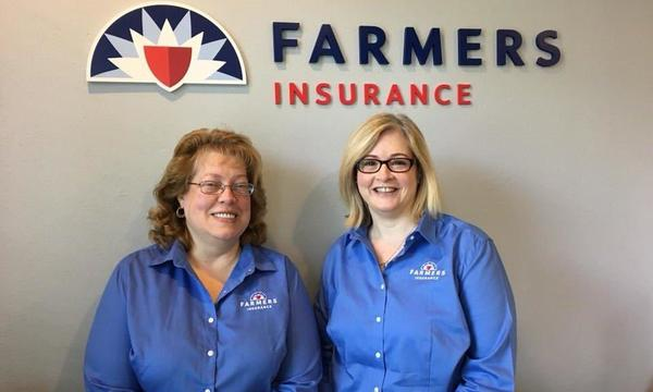Two women in Farmers uniforms underneath the Farmers Insurance logo.