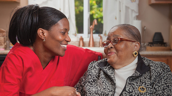 A Bayada Health care employee smiles with an elderly woman.