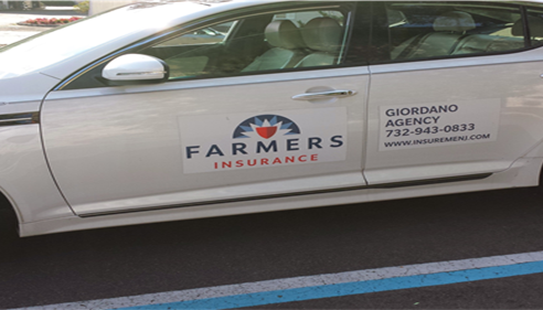 Grey car with a Farmers Logo on it.