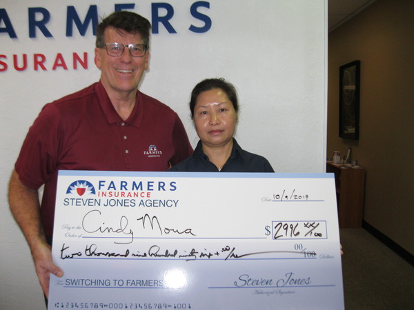 Two people are standing in front of the Farmers logo holding a big check