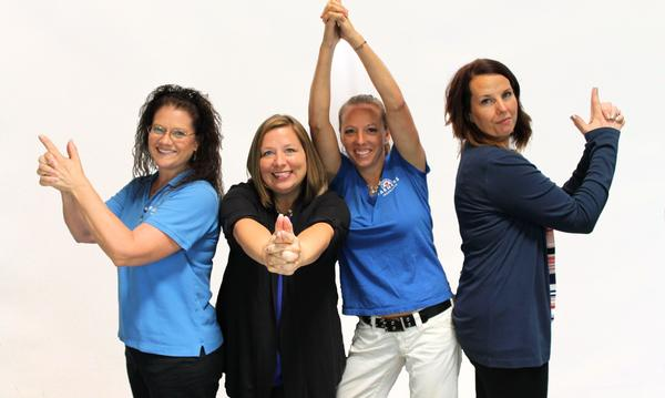 Four women doing goofy poses looking at the camera smiling
