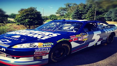 A blue NASCAR car is parked outside