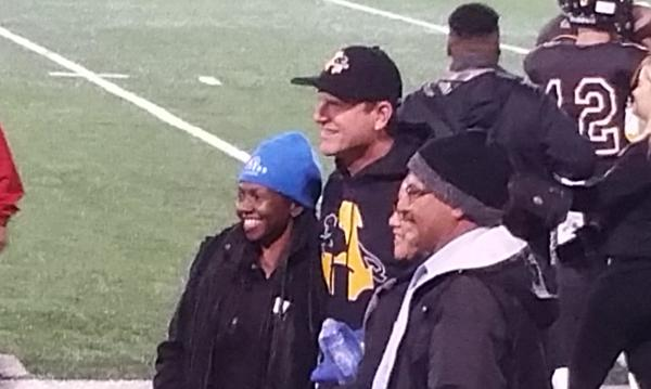 Agent Felicia Traylor standing with three people on the sidelines of a football game.