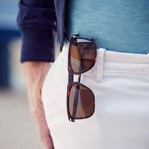 Designer sunglasses hanging in woman's pocket