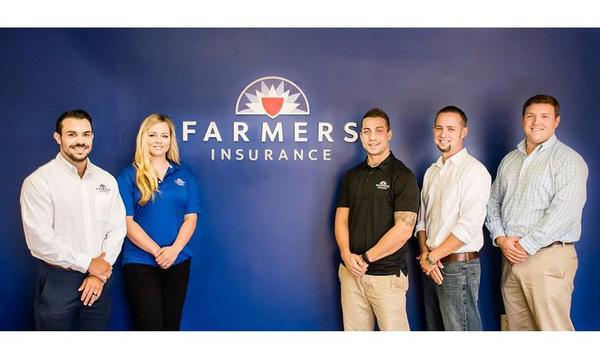 Agent Matthew Green and his staff in front the Farmers Insurance logo.