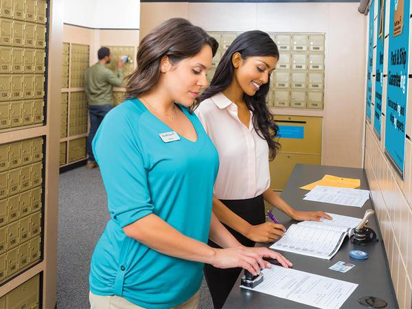 a notary public at The UPS Store helping a customer notarize her documents