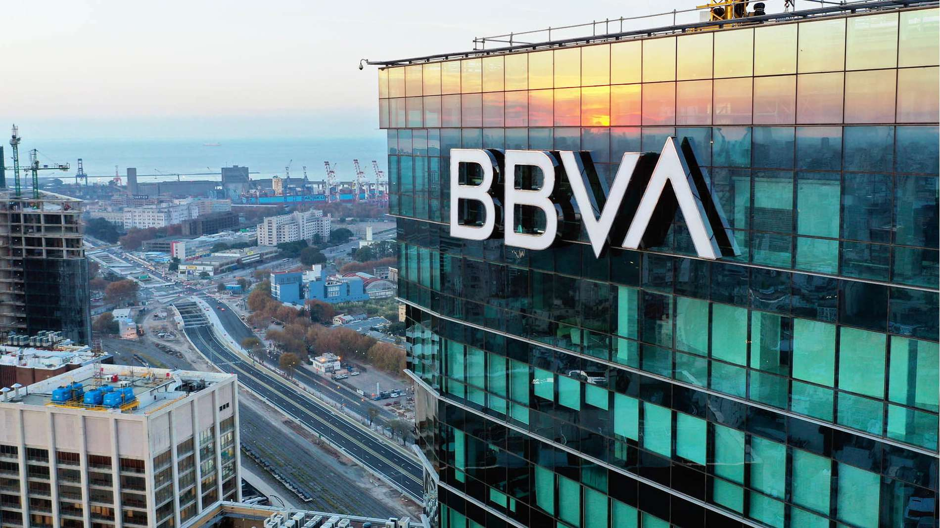 A Skyscraper with the BBVA USA Logo reflects sunset