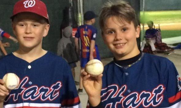 Two young boys in baseball uniforms.