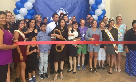 Photo of agent cutting a red ribbon with giant scissors, surrounded by many people.