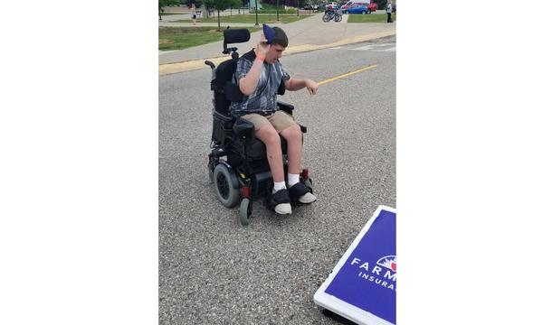 young man in a wheelchair playing corn hole.
