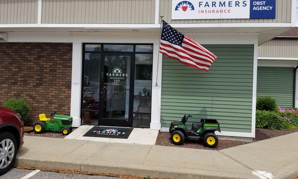 storefront with glass door with a garage door on the right. A toy truck in front with an american flag.