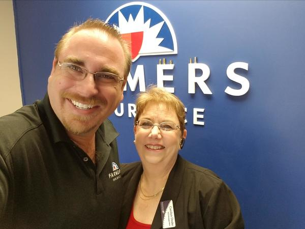 Agent and woman photo standing in front of Farmers® logo