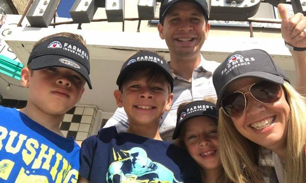 Agent, his wife and 3 children wearing Farmers Insurance caps.