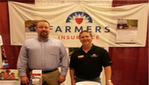 Two men are standing in front of a Farmers Insurance booth at a large expo or event
