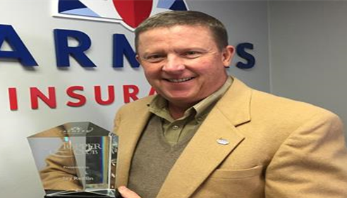 Agent standing in front of Farmers Insurance logo holding Topper Club award