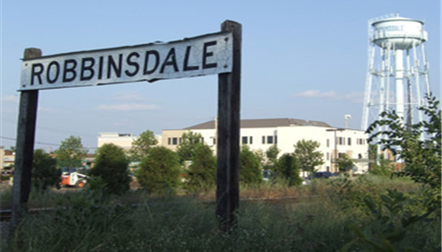 A sign for Robinsdale, with a water tower in the background