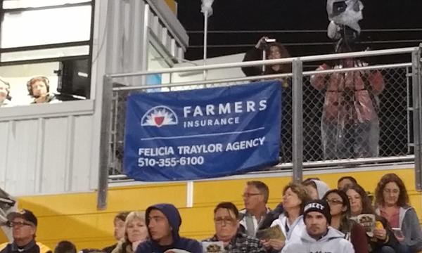 Felicia Traylor Agency banner displayed in the stands at a sporting event.