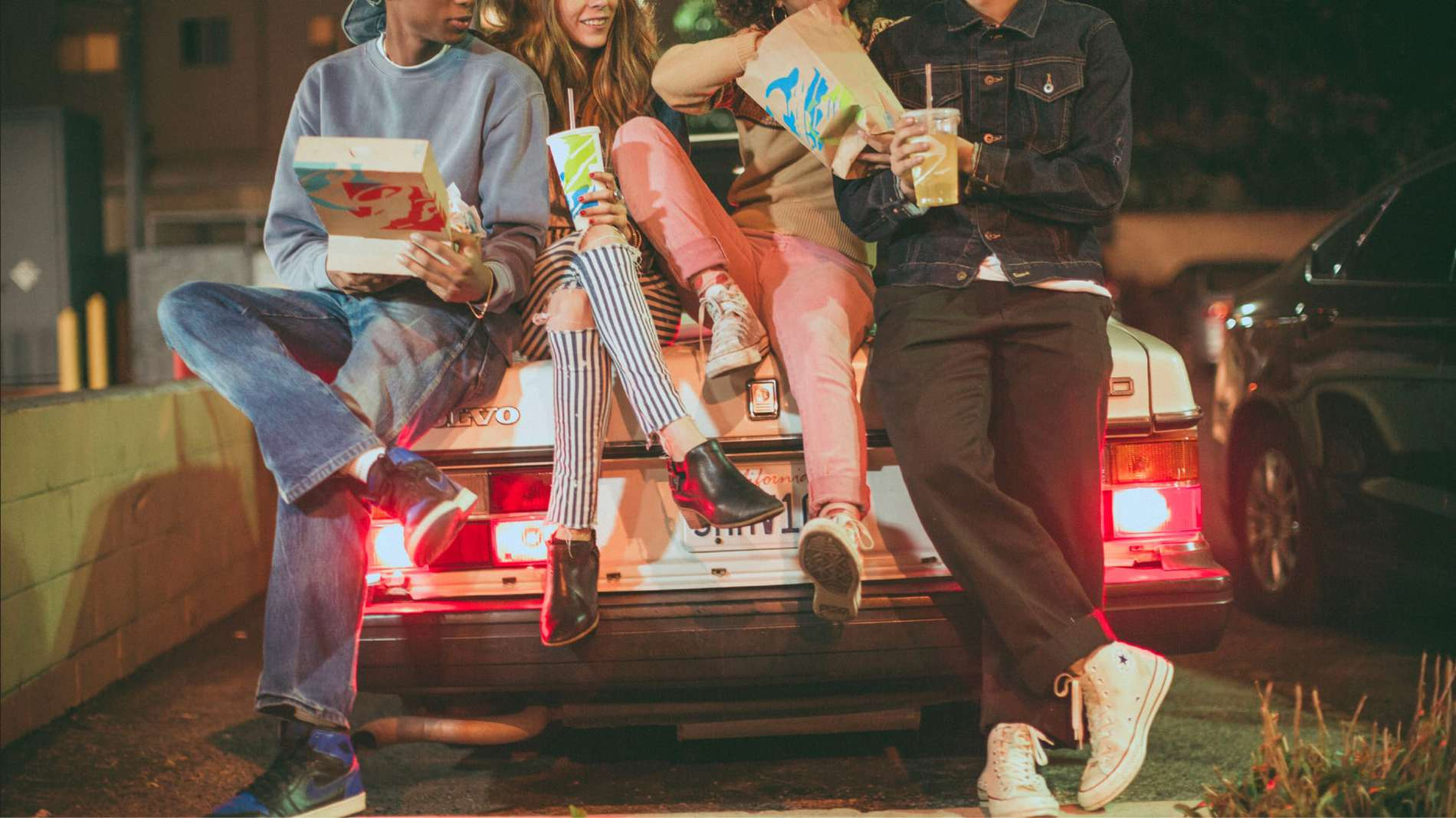 Three young people leaning against the trunk of the car while eating Taco Bell.