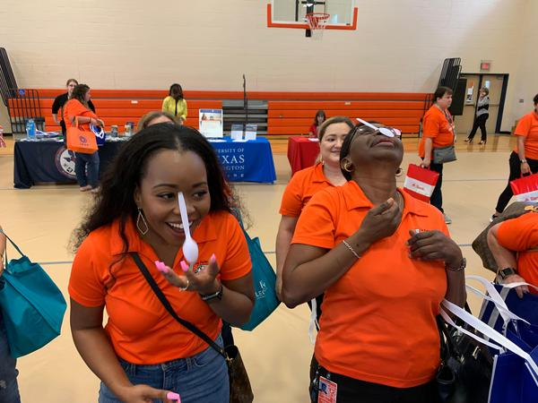 Two women in orange shirts balancing spoons on their noses