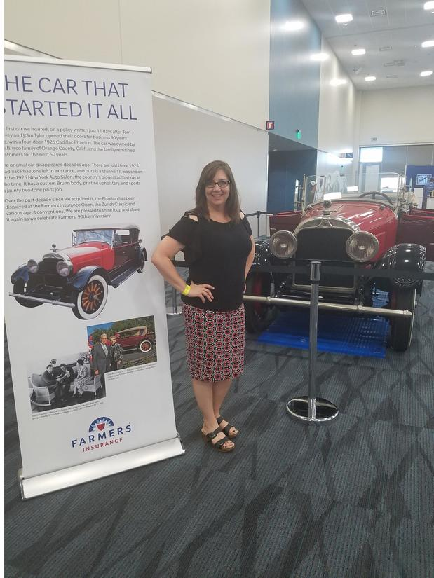 Photo of Denise standing next to the first car Farmers Insurance ever insured. A red vintage car.