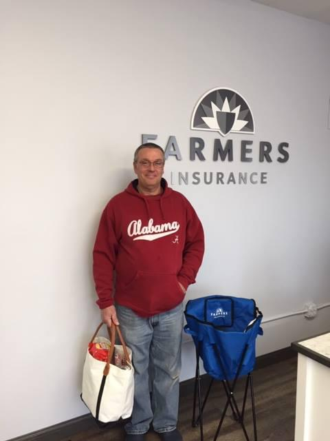 Man standing in front of Farmers Insurance logo