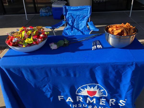 """Thank All Of The Amazing Mothers"" giveaways, Farmers Insurance table set up with food."