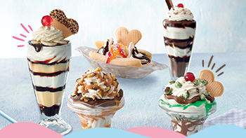 Four sundaes of various flavours on a blue table.