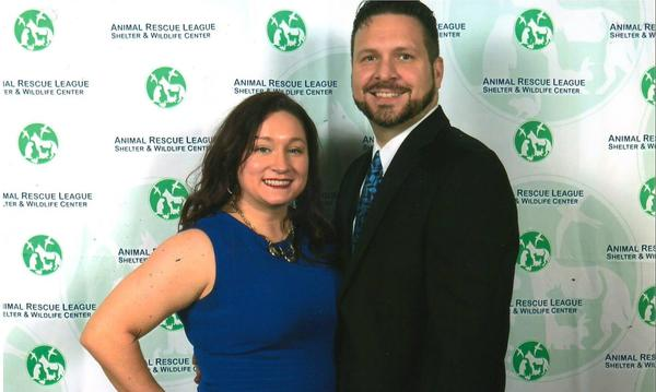The agent posing with a staff member in front of a backdrop of the Animal Rescue League