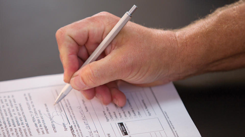 hand with pen filling out a paper document on a counter