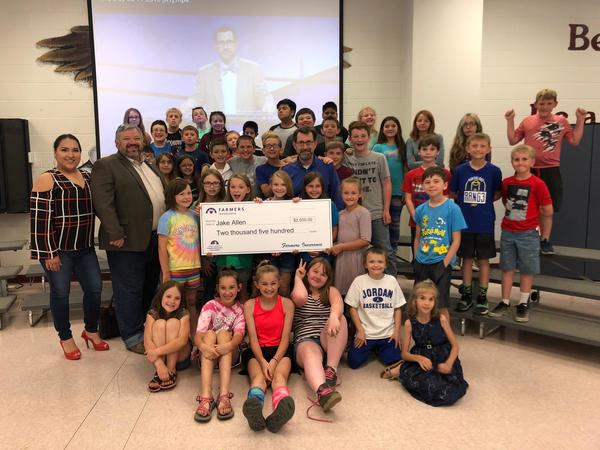 Agent standing with teacher and his class, holding a giant check.
