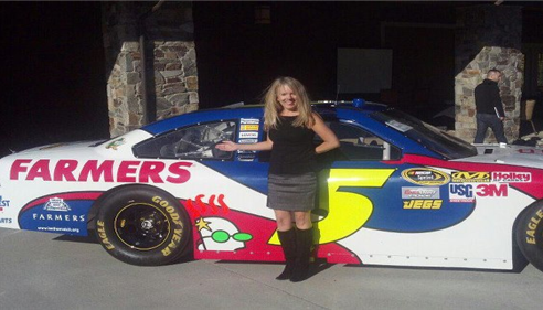 Isabelle poses in front of a NASCAR race cars