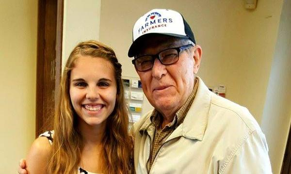 A young girl and an old man are looking at the camera and smiling.  The man is wearing a cap.