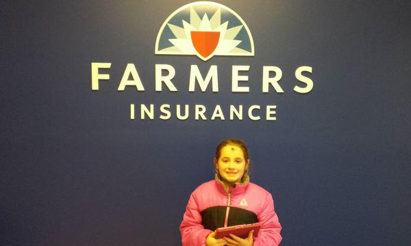 young girl in front of farmers logo