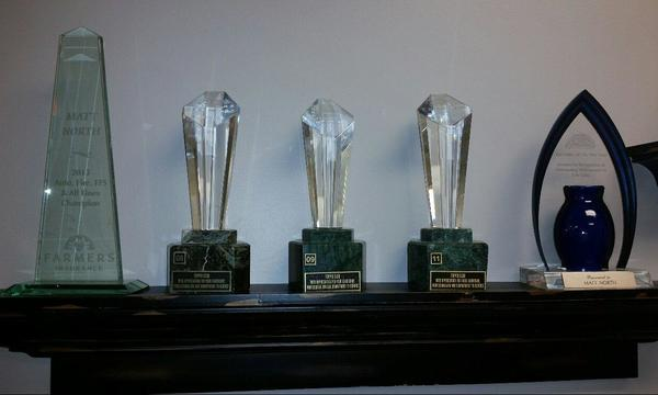 Five awards on a shelf.