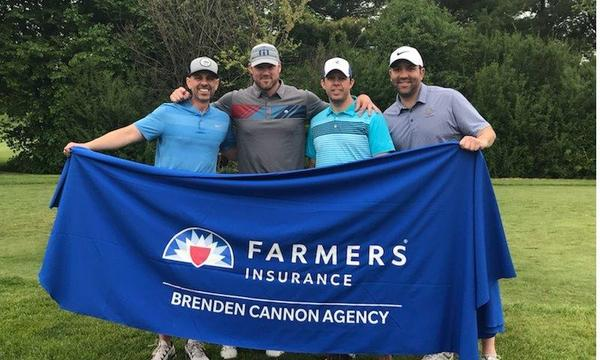 Four men holding a Farmers insurance banner