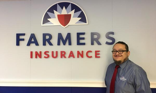 Male staff member standing in front of the Farmers Insurance logo