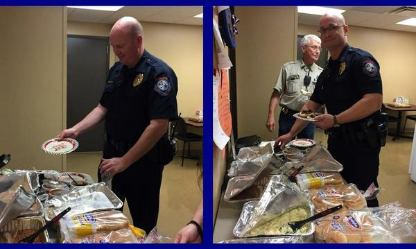 Police officers of Bixby, lining up to enjoy a buffet of food.