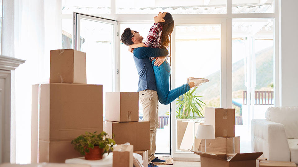 A happy young couple surrounded by moving boxes in their new home.